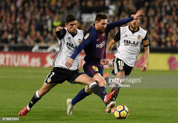 TOPSHOT Valencia's Portuguese midfielder Manuel Guedes vies with Barcelona's Argentinian forward Lionel Messi during the Spanish league football...
