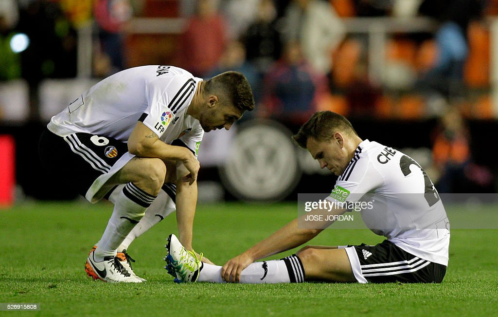 Valencia's Russian midfielder Denis Cheryshev (R) sits injured on te field past Valencia's Brazilian defender Guilherme Siqueira during the Spanish league football match Valencia CF vs Villarreal CF at the Mestalla stadium in Valencia on May 1, 2016. / AFP / JOSE