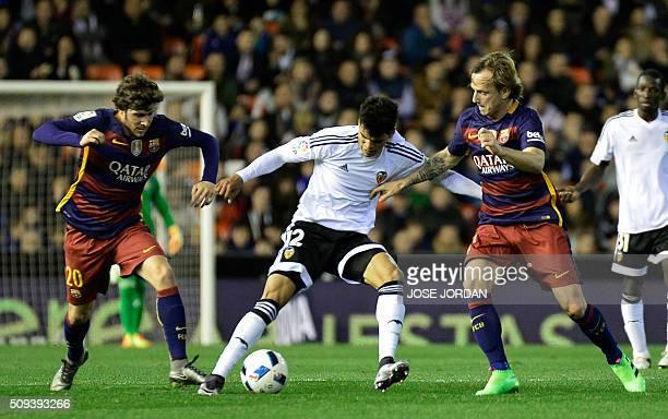 Valencia's Salvadoran midfielder Danilo Barbosa vies with Barcelona's midfielder Sergi Roberto and Barcelona's Croatian midfielder Ivan Rakitic...