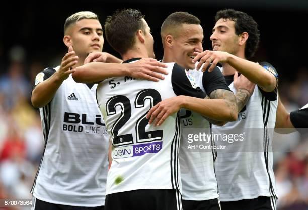 Valencia's Spanish forward Santi Mina celebrates a goal with Valencia's Brazilian forward Rodrigo Moreno Valencia's Spanish midfielder Dani Parejo...