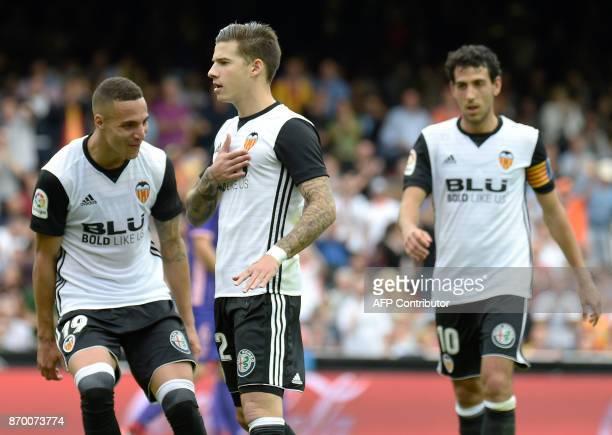 Valencia's Spanish forward Santi Mina celebrates a goal with Valencia's Brazilian forward Rodrigo Moreno and Valencia's Spanish midfielder Dani...