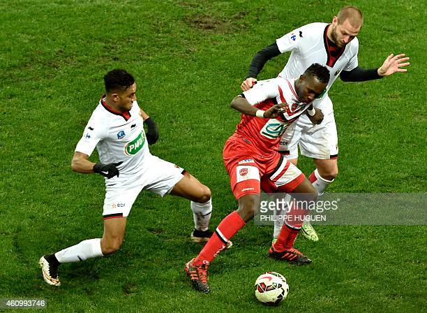 Valencienne's forward Abdoul Kabore vies for the ball with Nice's defender Mathieu Bodmer during the French Cup football match between Valenciennes...