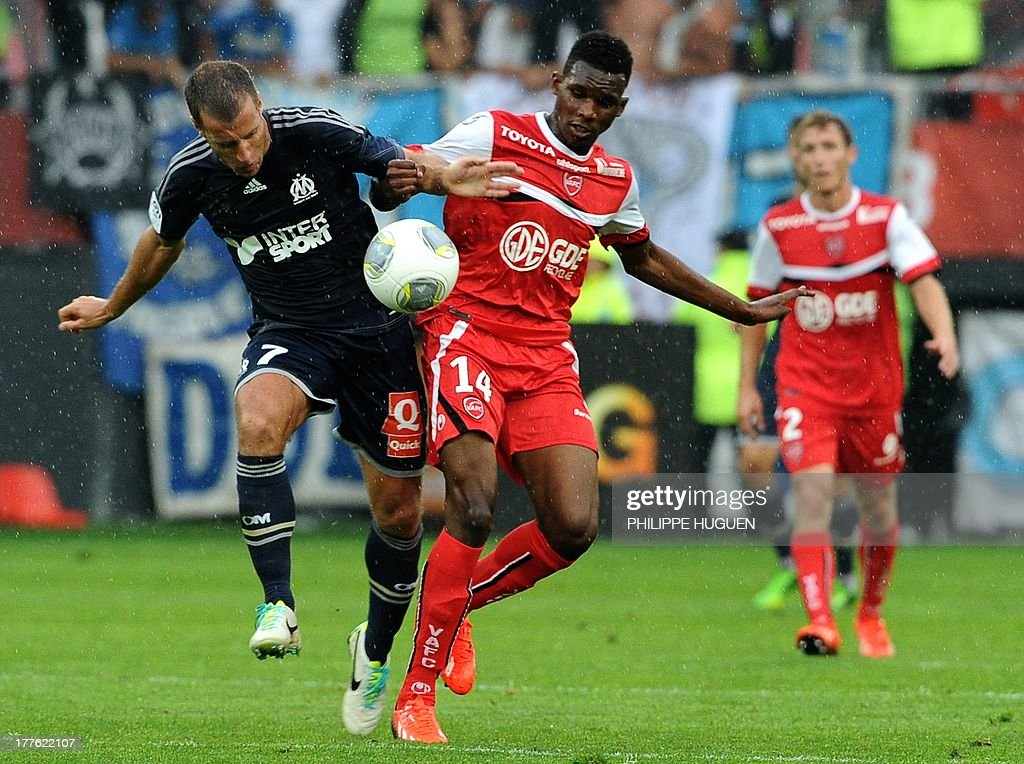 Valenciennes' French forward Opa Nguette (R) vies with Marseille's French midfielder Benoit Cheyrou during a French L1 football match between Valenciennes and Marseille on August 24, 2013 at Stade du Hainaut in Valenciennes.