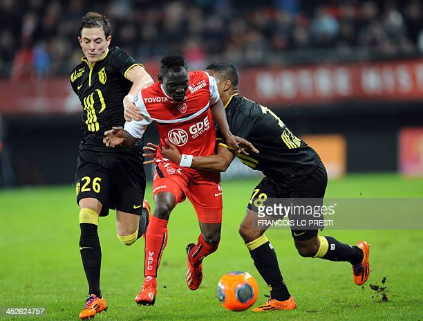 Valenciennes' player Saliou Ciss vies for the ball with Lille's French forward Nolan Roux and Lille's Argentinian defender Mauro Cetto during the...