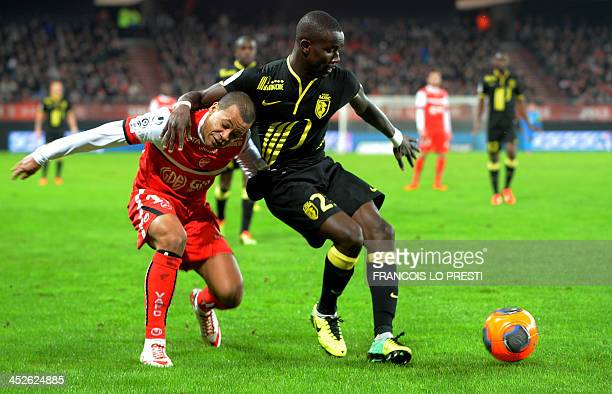 Valenciennes' s Matthieu Dossevi vies for the ball with Lille's Senegalese defender Pape Souare during a French L1 football match between...