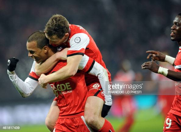 Valenciennes's Mathieu Dossevi is congratulated by teammates after scoring a goal during the French L1 football match Valenciennes vs Bastia at the...
