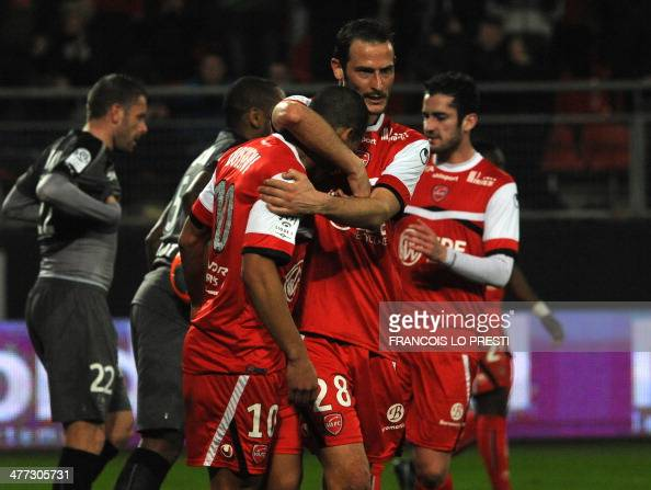 Valenciennes's Matthieu Dossevi is congratulated by teammates after scoring during the French L1 football match Valenciennes vs Rennes at the Stade...