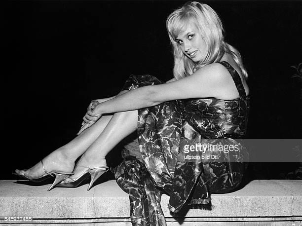 Valentin Barbara * Schauspielerin Oesterreich Ganzkoerperaufnahme sitzt auf einer Mauer traegt ein Kleid und hochhackige Schuhe 1960