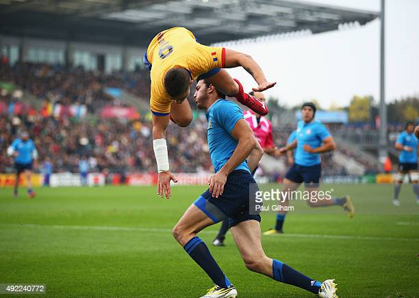 Valentin Calafeteanu of Romania leaps over Leonardo Sarto of Italy as he scores the opening try during the 2015 Rugby World Cup Pool D match between...
