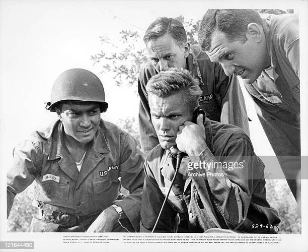 Valentin DeVarger Henry Jones and Alan King surround Tab Hunter who's on the phone in a scene from the film 'The Girl He Left Behind' 1956