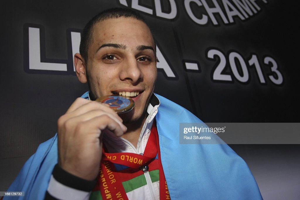 Valentin Hrsitov bites his gold medal after setting a new junior world record in Mens 62 kg during day two of the 2013 Junior Weightlifting World Championship at Maria Angola Convention Center on April 05, 2013 in Lima, Peru.