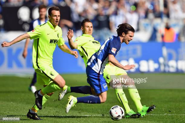 Valentin Stocker of Berlin is challenged by Christoph Janker and Dominik Kohr of Augsburg during the Bundesliga match between Hertha BSC and FC...