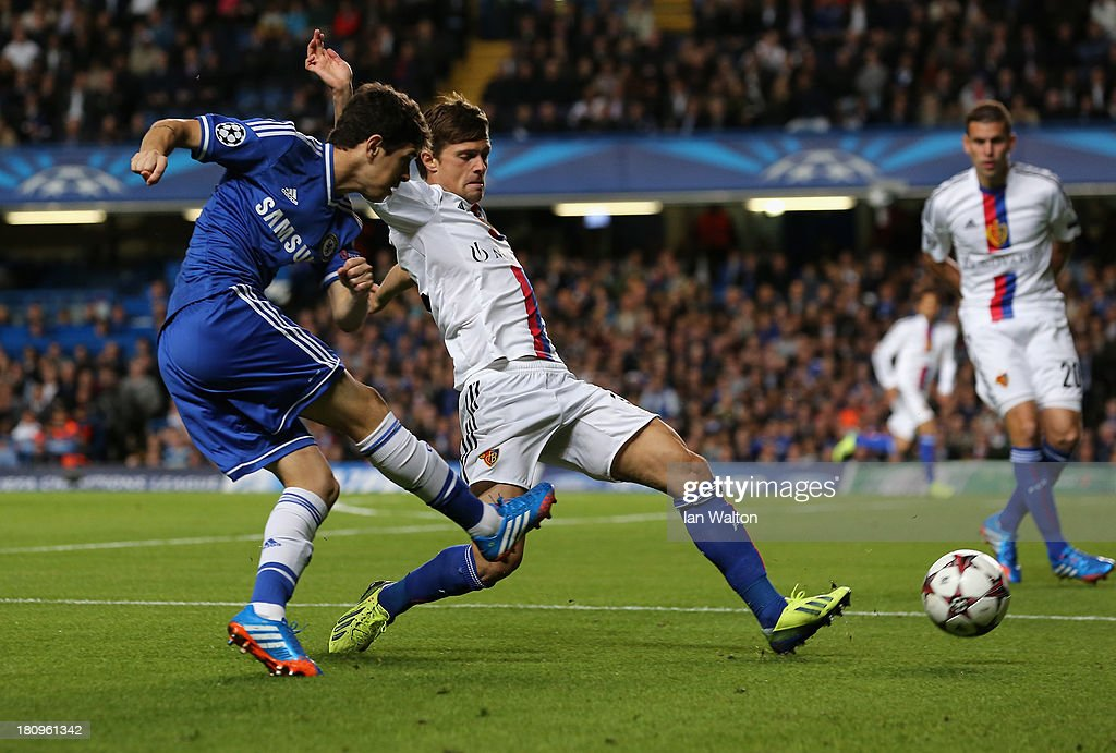 Valentin Stocker of FC Basel attempts to block as Oscar of Chelsea crosses the ball during the UEFA Champions League Group E Match between Chelsea and FC Basel at Stamford Bridge on September 18, 2013 in London, England.