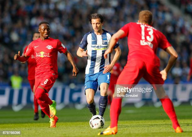 Valentin Stocker of Hertha BSC is challenged by Naby Keita of RB Leipzig and Stefan Ilsanker of RB Leipzig during the Bundesliga match between Hertha...