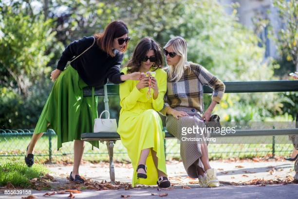 Valentina Siragusa and Eleonora Carisi wearing neon dress and Linda Tol sitting on a bench looking at a mobile phone seen outside Issey Miyake during...
