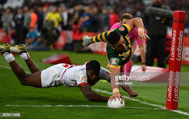 Valentine Holmes of Australia scores in the corner despite the efforts of Jermaine McGillvary of England during the Four Nations match between the...