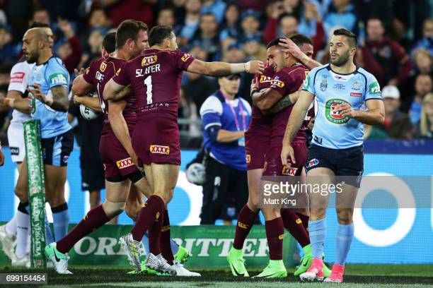 Valentine Holmes of the Maroons celebrates with team mates after scoring a try during game two of the State Of Origin series between the New South...