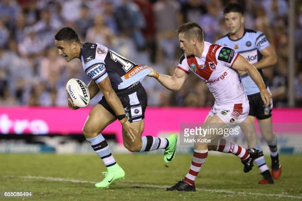 Valentine Holmes of the Sharks tries to beat the tackle of Josh McCrone of the Dragons during the round three NRL match between the Cronulla Sharks...