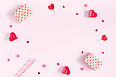 Valentine's Day. Frame made of gifts, candles, confetti on pink background. Valentines day background. Flat lay, top view, copy space