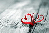 Red ribbon in heart shape at wooden background