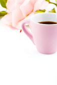 White background with pink cup of coffee and rose flower. Romantic Valentines Day backdrop with copy space in pastel color