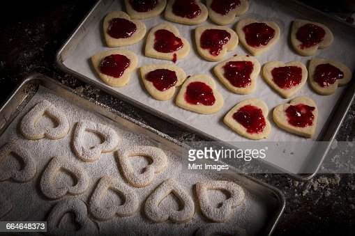 Valentines Day baking, woman spreading raspberry jam on heart shaped biscuits.