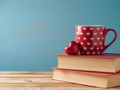 Valentines day concept with cup, heart shape and books over rustic background
