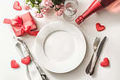 Valentines day dinner with table place setting with red gift, glass for champagne, a bottle of champagne, pink roses, hearts with silverware on white background. View from above. Valentine's card.