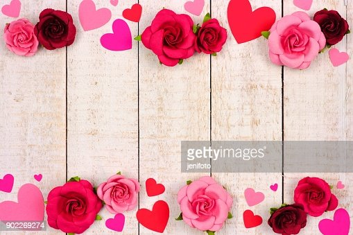 Valentines Day double border of hearts and roses against rustic white wood : Stock Photo