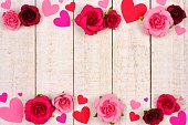 Valentines Day double border of red and pink paper hearts and roses against a rustic white wood background with copy space.