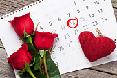 Valentines day greeting card. Red roses and hearts over february calendar on wooden table. Top view