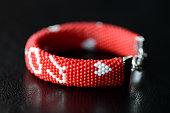 Valentine's Day red beaded bracelet on a dark background close up