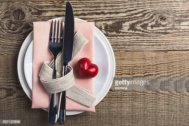 Valentines day table setting with knife, fork, ribbon and heart, top view