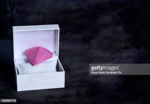 Valentine's heart in a open gift box. Origami Heart done with pink polka dot paper. Subject captured against soft window lighting over abstract background with copy space.