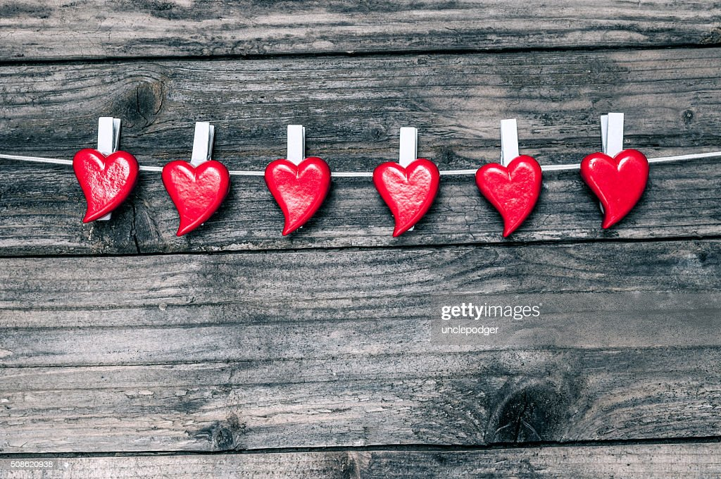 Valentine`s hearts  hanging over gray wooden background : Stock Photo