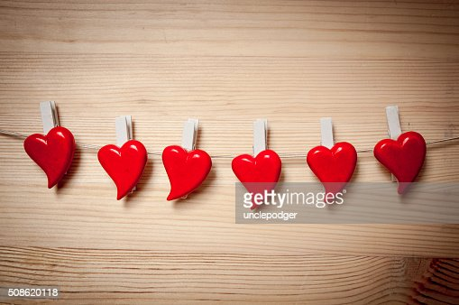 Valentine`s hearts  hanging over wooden background : Stock Photo