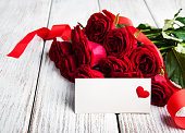 Box with roses and card on a old wooden background