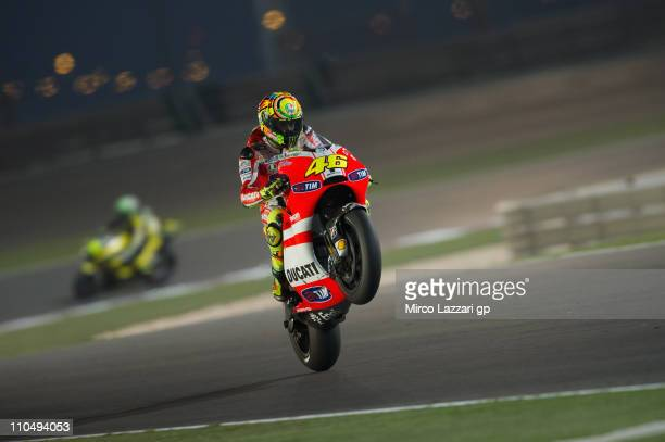 Valentino Rossi of Italy and Ducati Marlboro Team lifts the front wheel at the end of MotoGP race of MotoGP of Qatar at Losail Circuit on March 20...