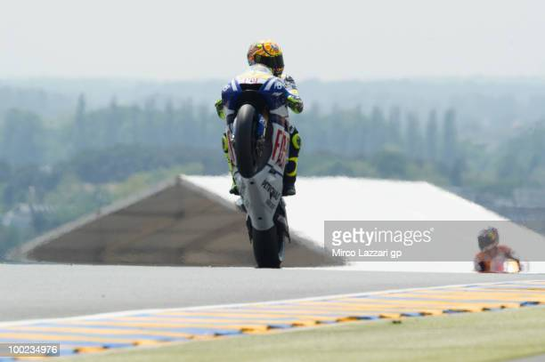 Valentino Rossi of Italy and Fiat Yamaha Team lifts the front wheel in order to celebrate the Pole Position at the end of the qualifying practice...