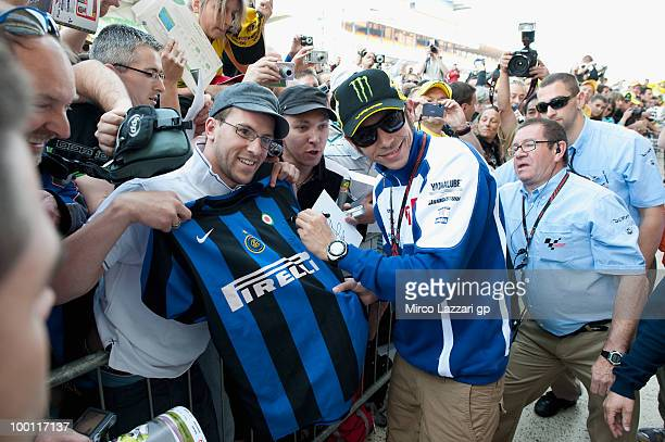Valentino Rossi of Italy and Fiat Yamaha Team signs autographs for fans in the 'Inter Tshirt' during the 'Pit Lane Walk' of the MotoGP French Grand...