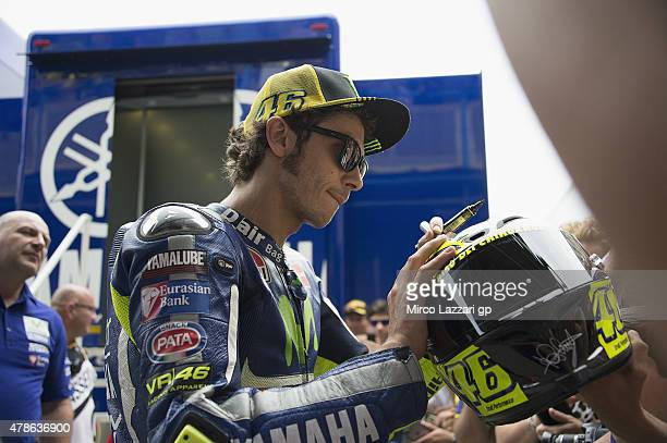 Valentino Rossi of Italy and Movistar Yamaha MotoGP signs autographs for fans during the MotoGP Netherlands Qualifying at TT Assen Circuit on June 26...