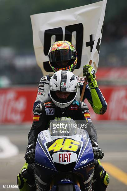 Valentino Rossi of Italy and the Fiat Yamaha Team is chauffeured back to the pits by Angel Nieto after he equalled his race win record of 90 wins...