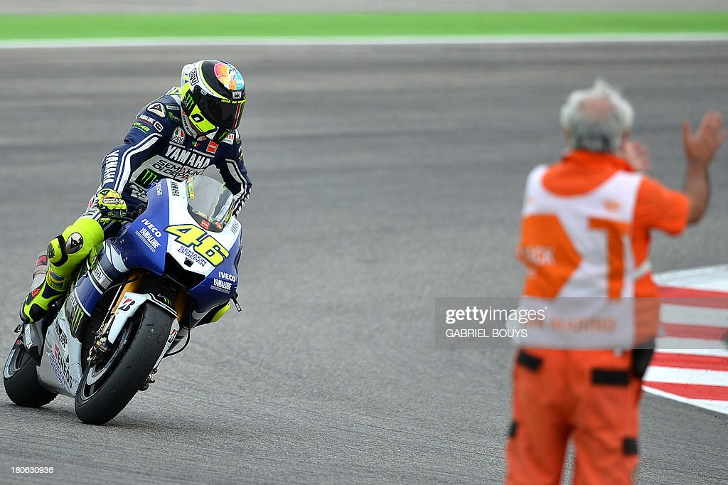 Valentino Rossi of Italy rides back to the stand after taking the fourth place during the San Marino MotoGP Grand Prix on September 15, 2013 at the Misano world circuit in Misano Adriatico. Yamaha rider Jorge Lorenzo of Spain won the race ahead of Spanish Honda riders Marc Marquez, second place and Dani Pedrosa, third. AFP PHOTO / GABRIEL BOUYS