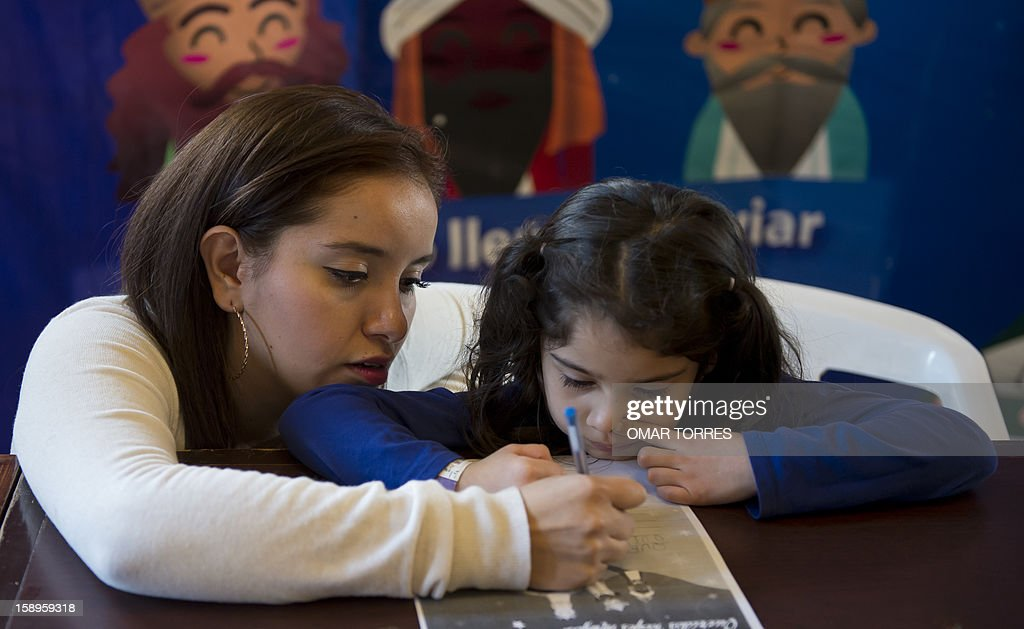 Valentins Talavera (R)and her godmother Maria Fernanda Garrido (L) write a letter to the Three Kings at the main post office in Mexico City on January 4, 2013. In Spanish-speaking parts of the world, children believe that the Three Kings receive their letters and so bring them gifts on the night before Epiphany. The Mexican Post Office opened this service to encourage the use of traditional mail. AFP PHOTO/OMAR TORRES