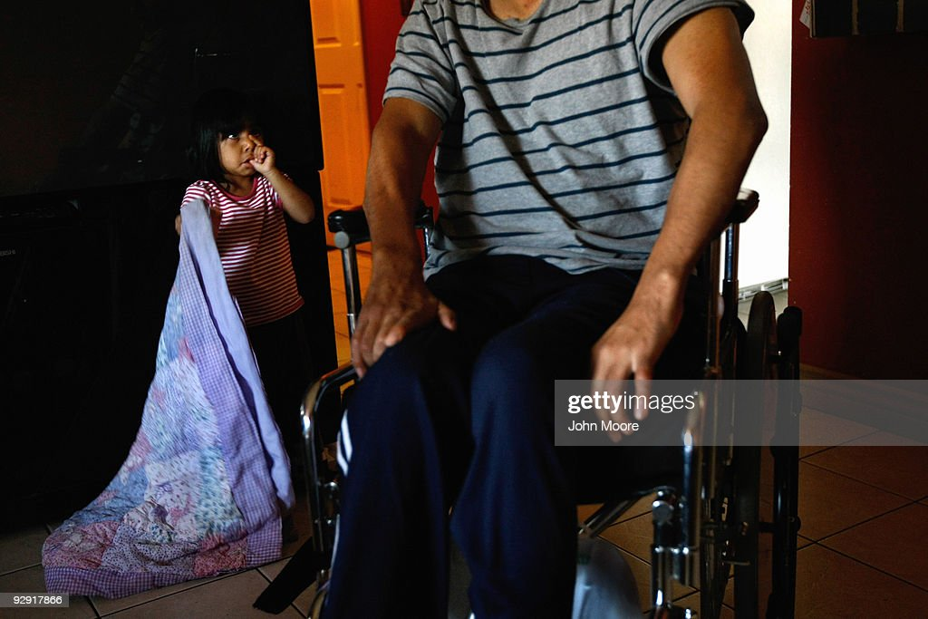 Valeria Lopez (L), 2, looks to her father Miguel Lopez, largely paralyzed from the chest down, at home on November 9, 2009 in Lakewood, Colorado. Lopez, a Mexican immigrant whose three children were born in the United States and are American citizens, broke his neck last summer while playing with his daughters on a backyard trampolene. Formerly a construction worker, Lopez had no health insurance when the accident occurred. He receives home health care visits from Dominican Sisters Home Health Agency, a non-profit that performs some 25,000 home visits each year in the Denver area. It provides free home nursing care to patients with chronic diseases, helps them to better manage their disabling illnesses and provides custodial services with the aim of keeping patients in their homes and out of more expensive nursing home care.