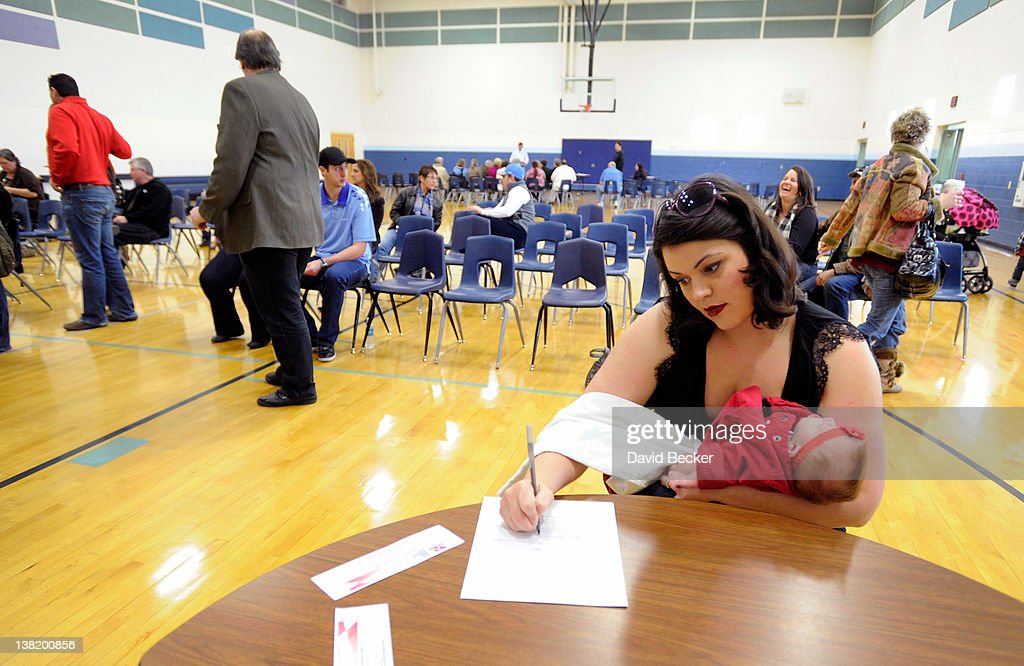 Valerie Pachpulski, holding her daughter, Stella Gallagher fills out paperwork during the Republican caucus at Centennial High School on February 4, 2012 in Las Vegas, Nevada. Nevada is the first state in the West to vote as Republicans go about choosing their presidential candidate.