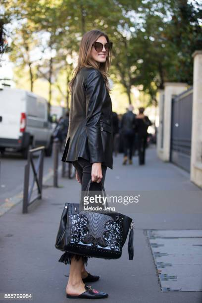 Valery Kaufman wears an all black outfit including a black leather jacket black Balmain bag and Gucci loaers on September 29 2017 in Paris France