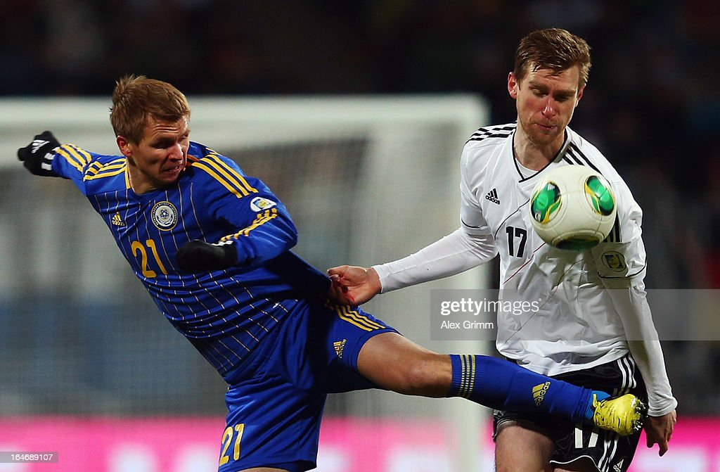 Valery Korobkin (L) of Kazakhstan is challenged by Per Mertesacker of Germany during the FIFA 2014 World Cup qualifier between Germany and Kazakhstan at Grundig-Stadion on March 26, 2013 in Nuremberg, Germany.