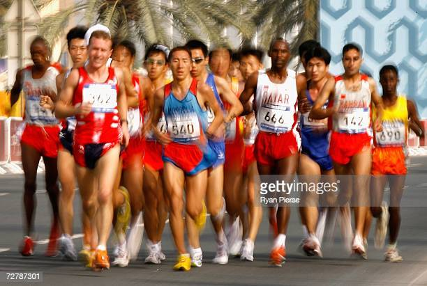 Valery Pisarev of Kyrgyzstan leads a group of athletes in the Men's Marathon Final during the 15th Asian Games Doha 2006 at Qatar at the Marathon...