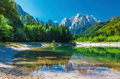 Valley with the lake in the Triglav National Park. The water surface reflects the surrounding mountains in Julian Alps , Slovenia
